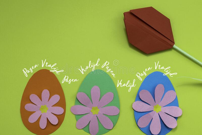 Vrolijk Pasen, Dutch words for Happy Easter with paper eggs and flowers royalty free stock photography
