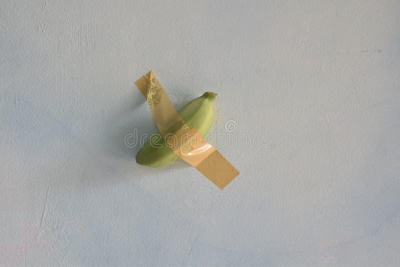 Duto de banana verde colado na parede foto de stock royalty free