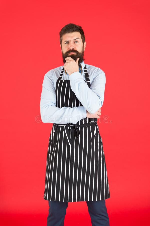 On duty in kitchen. Hipster cafe concept. Man with beard cook hipster apron. Hipster chef cook red background. Bearded. On duty in kitchen. Man with beard cook royalty free stock images