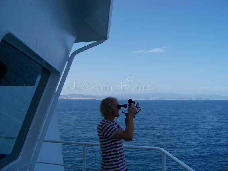 Working with sextant on merchant ship at sea stock photography