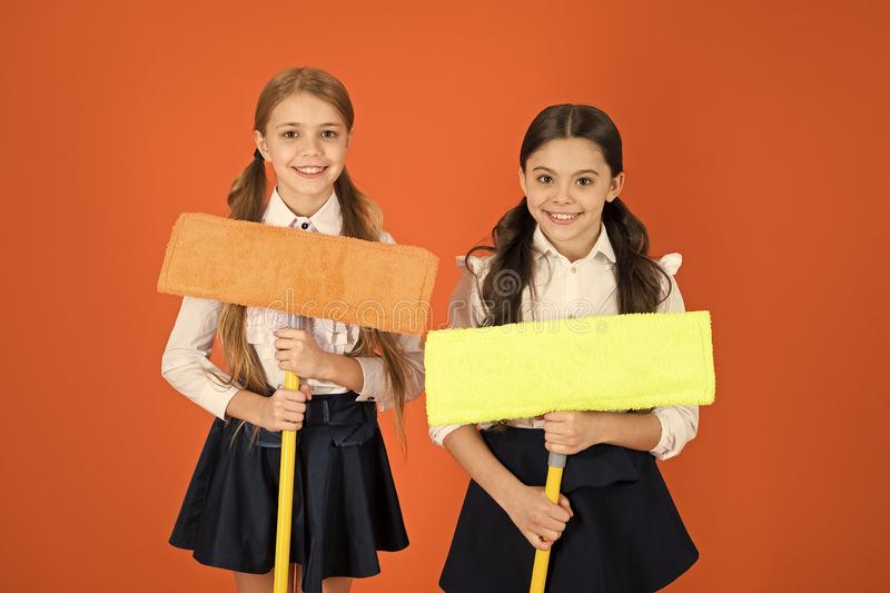 We are on duty today. Pupil cleaning classroom. Nice and tidy. Schoolgirls mop ready for cleaning. School duties. Little. Helper. Girls cute kids school uniform royalty free stock images