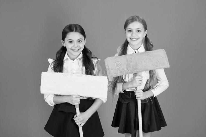 We are on duty today. Pupil cleaning classroom. Nice and tidy. Schoolgirls mop ready for cleaning. School duties. Little. Helper. Girls cute kids school uniform stock photo
