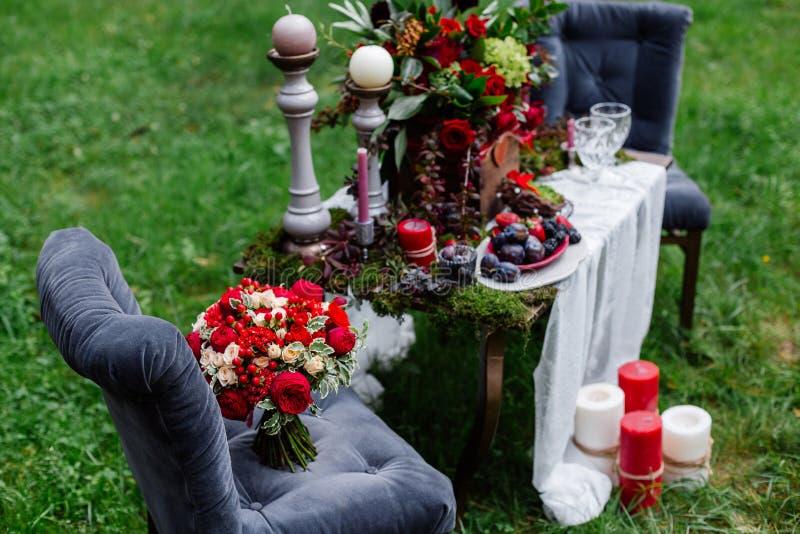 Duur, in huwelijksboeket van rozen in marsala en rode kleuren die zich op stoel bevinden Bruids details en decor met bloemen stock fotografie