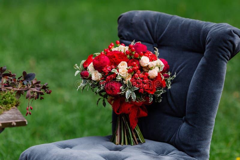 Duur, in huwelijksboeket van rozen in marsala en rode kleuren die zich op stoel bevinden Bruids details en decor met bloemen royalty-vrije stock afbeelding
