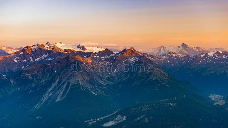 Duur zacht zonlicht over rotsachtige bergpieken, randen en valleien van de Alpen bij zonsopgang Extreem terreinlandschap bij hoge royalty-vrije stock fotografie
