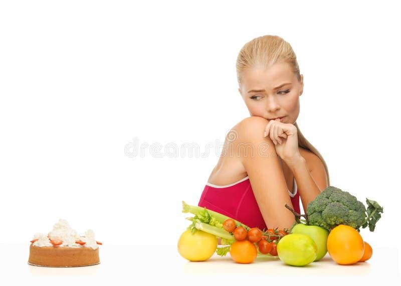 Duvidando a mulher com frutos e Hamburger foto de stock