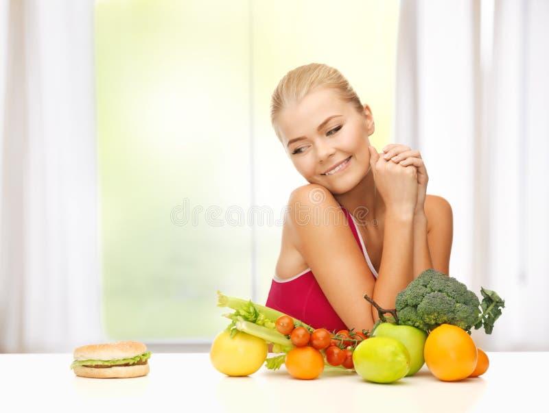 Duvidando a mulher com frutos e Hamburger imagem de stock royalty free