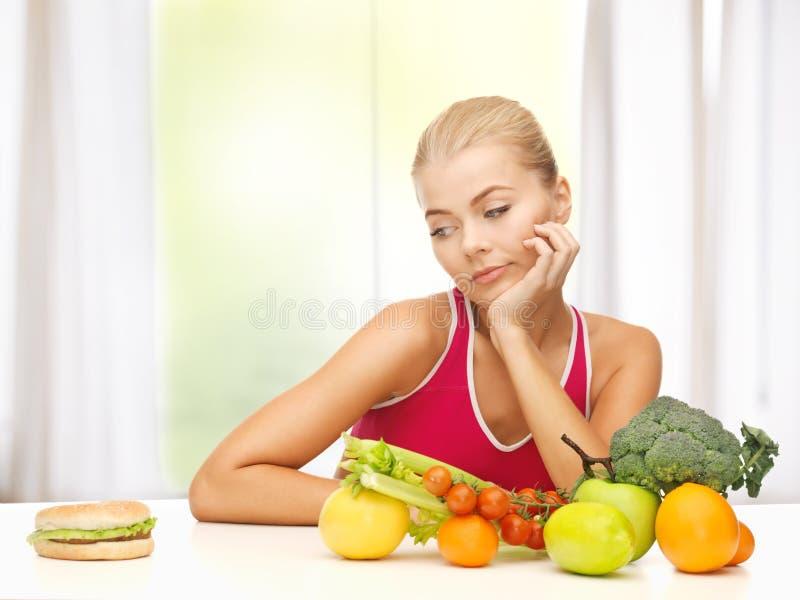 Duvidando a mulher com frutos e Hamburger fotografia de stock