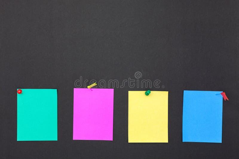 Duwspelden en Kleurrijke kleverige nota's over het lege bord royalty-vrije stock afbeeldingen