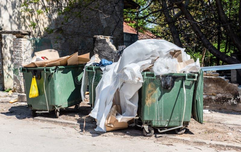 Duzi śmietników pojemniki na śmiecie pełno przelew ściółka zanieczyszcza ulicę w mieście z dżonką i gratem obraz royalty free