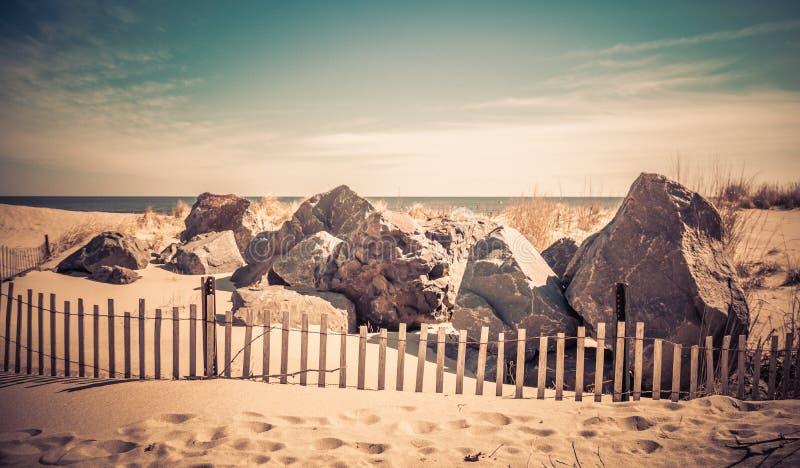 Duzi głazy i palika ogrodzenie wzdłuż plaży w oceanu gaju, NJ, na pogodnym zima dniu obraz stock