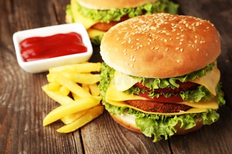 Duzi hamburgery na brown drewnianym tle zdjęcia stock