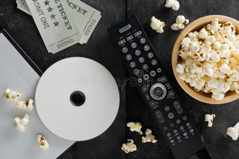 DVD or blu ray movie disc with tv remote control, movie tickets and bowl of popcorn on dark background. Home theatre movie or. Series night concept. Flat lay royalty free stock photo