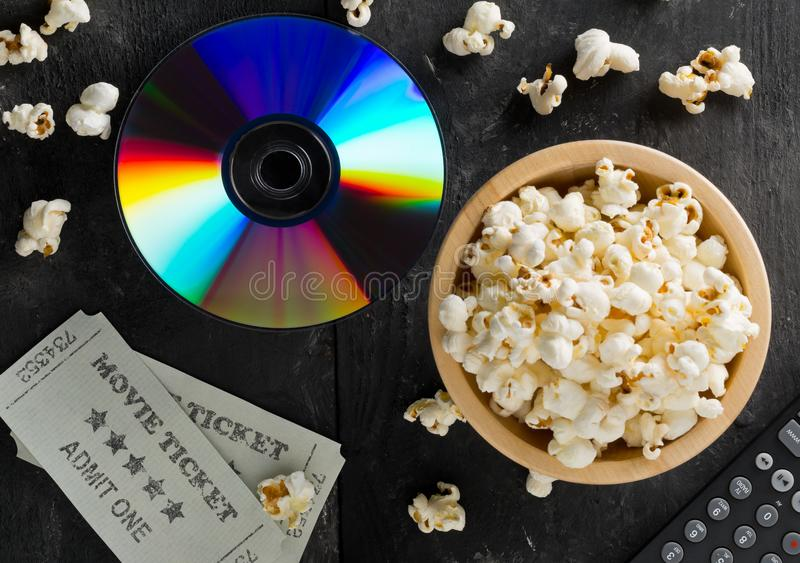 DVD o disco azul de la película del rayo con la TV teledirigida, boletos de la película y cuenco de palomitas en fondo oscuro Pel fotografía de archivo libre de regalías