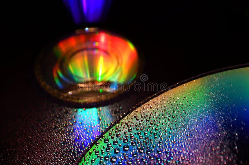 DVD och CD disketten med vattendroppar färgar bakgrund royaltyfria foton