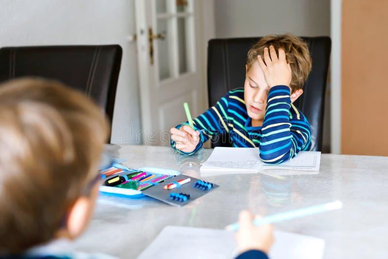 Dwóch ciężko pracujących dzieci w szkole chłopców odrabiających pracę domową podczas kwarantanny z powodu choroby Corona i pandem fotografia royalty free