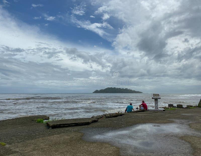 Dwóch mężczyzn siedzących na konkretnej krawędzi z widokiem na morze karaibskie w Puerto Limon, Kostaryka zdjęcie royalty free