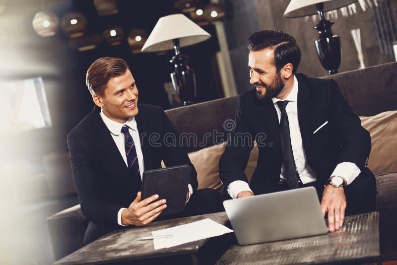 Dwóch partnerów biznesowych siedzących przy stole i uśmiechających się podczas rozmowy obrazy stock