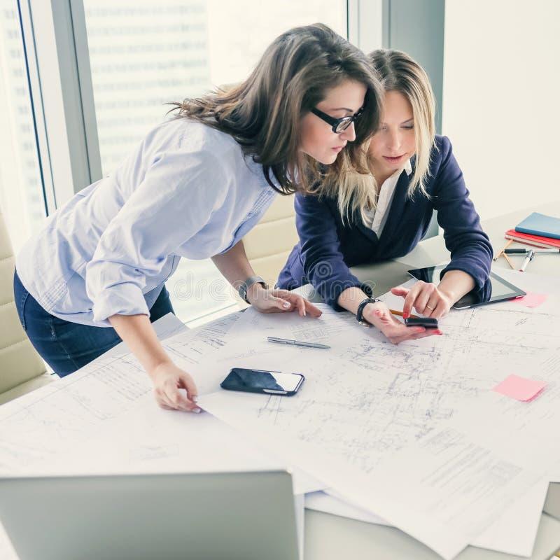 Dwa żeńskiego coworkers używa mądrze telefon podczas gdy pracujący na projekcie zdjęcie stock