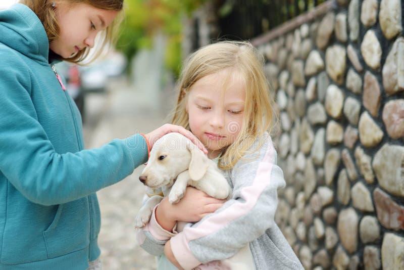 Dwa ślicznej młodej siostry trzyma małego białego szczeniaka outdoors Dzieciaki bawić się z dziecko psem na letnim dniu zdjęcia royalty free