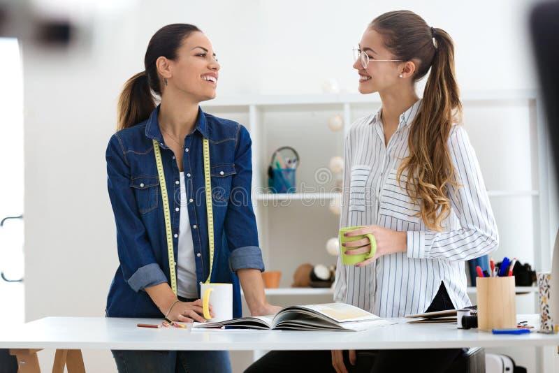 Dwa ładnego młodego bizneswomanu pije kawę podczas gdy brać przerwę w szwalnym warsztacie zdjęcie stock