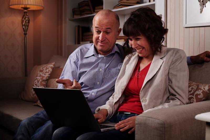 Dwa ładnego uśmiechniętego ludzie ogląda coś na laptopie zdjęcia stock