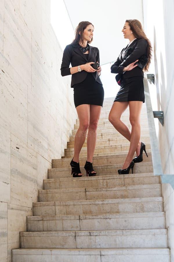 Dwa ładnej bizneswoman rozmowy na schodkach obrazy stock