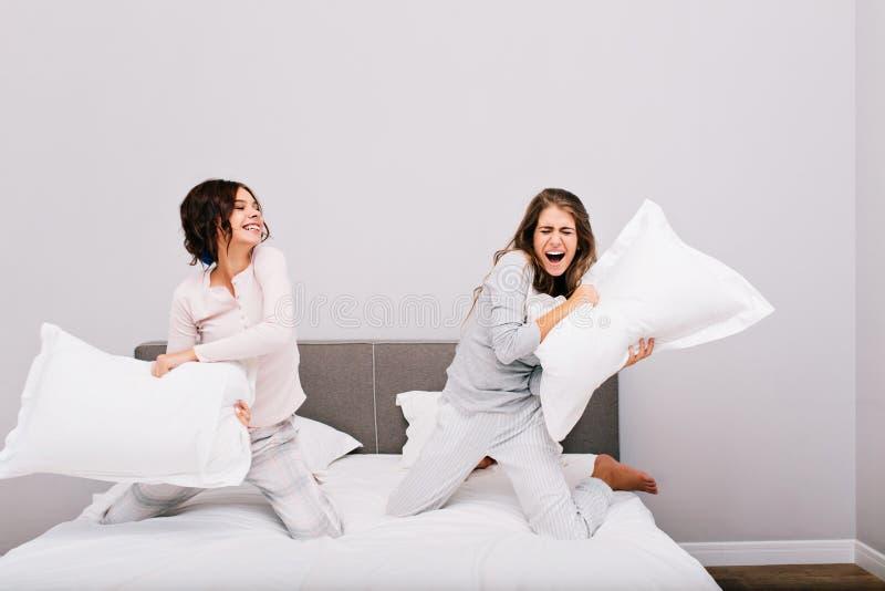 Dwa ładnej dziewczyny ma piżamy przyjęcia One walczy z poduszki walką na łóżku zdjęcie royalty free