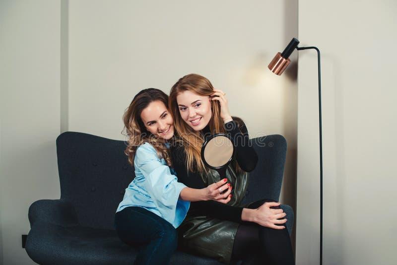 Dwa ładnej młodej kobiety siedzi na kanapie i patrzeje odzwierciedlać wewnątrz zdjęcia royalty free