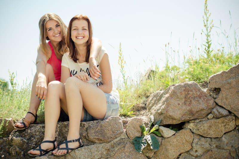 Dwa ładnej przyjaciół uśmiechniętej & patrzeją dziewczyny szczęśliwej kamery ma zabawę na letnim dniu outdoors obraz royalty free