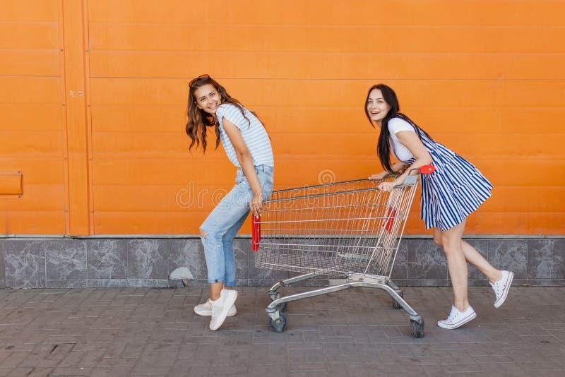 Dwa ładnej szczupłej ciemnowłosej damy, jest ubranym przypadkowego strój blisko centrum handlowego, stojak z sklep spożywczy furą obrazy stock