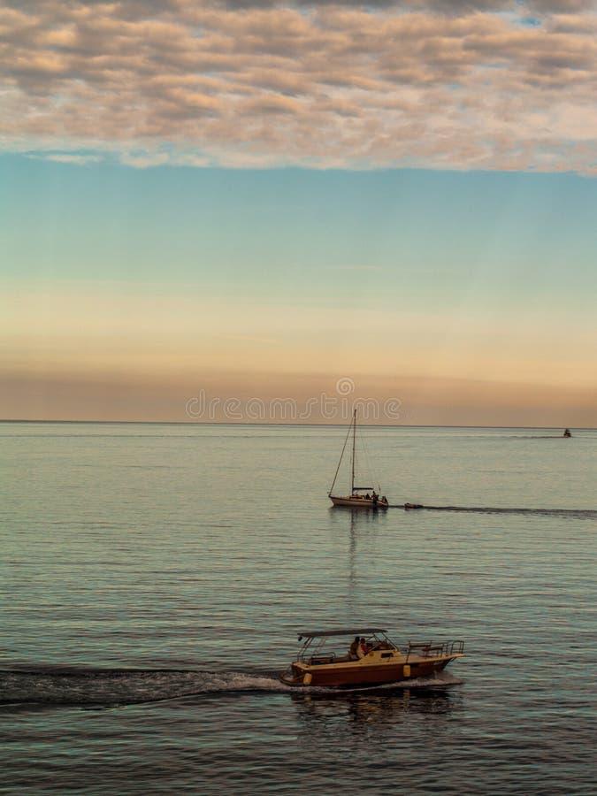 Dwa łodzi krzyżuje wokoło na Adrian morzu z chmurami i zmierzchem zdjęcia royalty free