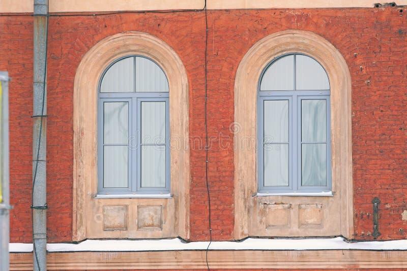 Dwa łukowatego okno w ceglanym domu obrazy stock