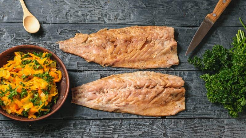 Dwa ścierwa makrela, puchar warzywa, nóż i łyżka na ciemnym drewnianym stole, obraz royalty free