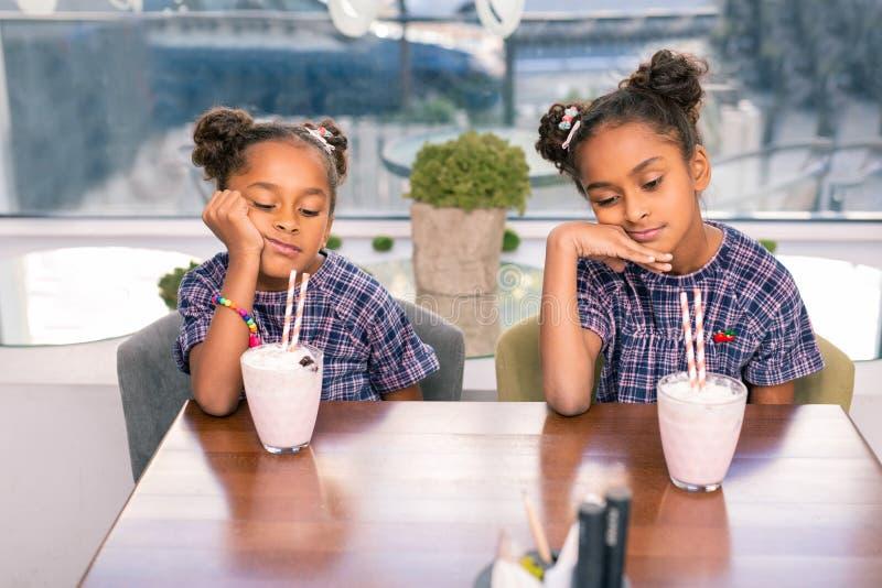Dwa ślicznego śmiesznego rodzeństwa jest ubranym ten sam sukni czuć zanudzam czekać na jedzenie zdjęcie stock