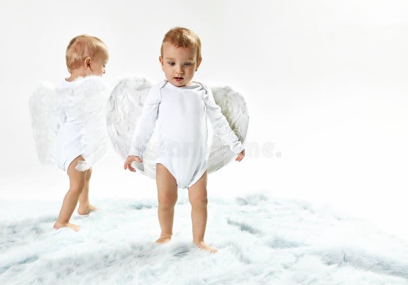Dwa ślicznego dziecko anioła chodzi na miękkim dywanie obraz stock