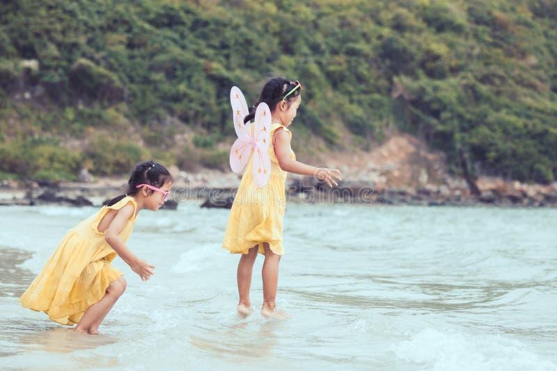 Dwa ślicznej azjatykciej małe dziecko dziewczyny bawić się i skaczą na plaży obrazy stock