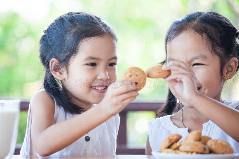 Dwa ślicznej azjatykciej małe dziecko dziewczyny jedzą ciastka z mlekiem obrazy stock