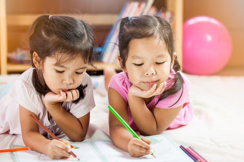 Dwa ślicznej azjatykciej małej dziewczynki odpoczywają ich podbródek na ich rękach zdjęcie stock