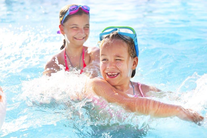Dwa ślicznej dziewczyny bawić się w pływackim basenie zdjęcia stock