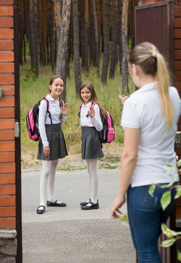 Dwa ślicznej dziewczyny opuszcza szkoła przy mnorning matkować i machać zdjęcia royalty free