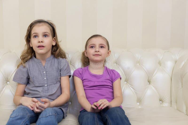Dwa ślicznej dziewczyny siedzi na kanapie i ogląda TV obraz stock