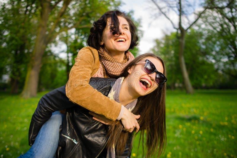 Dwa ślicznej młodej kobiety radośnie wydają czas w wiosna parku fotografia royalty free