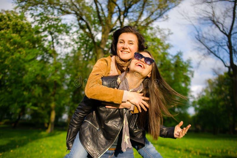 Dwa ślicznej młodej kobiety radośnie wydają czas w wiosna parku fotografia stock