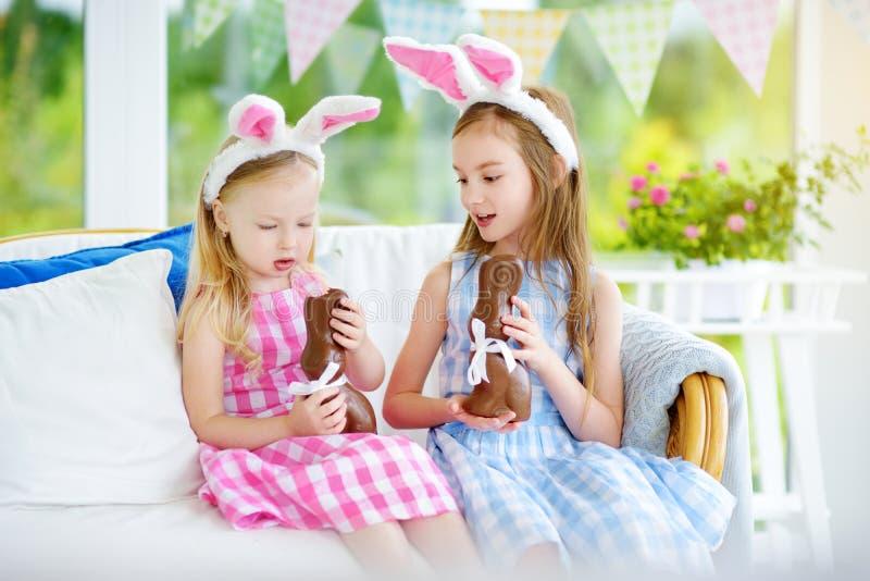 Dwa ślicznej małej siostry jest ubranym królików ucho je czekoladowych Wielkanocnych króliki Dzieciaki bawić się jajecznego polow obraz stock