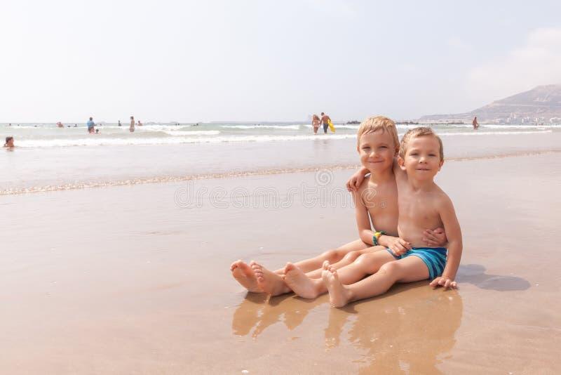 Dwa ślicznej uroczej młodszy brat chłopiec siedzi na plażowym oceanu morzu zdjęcia royalty free