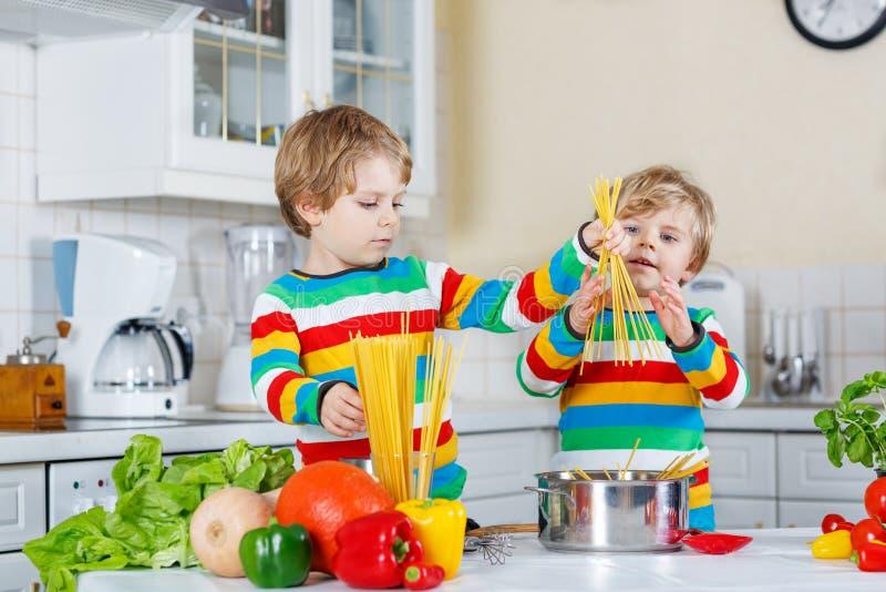 Dwa śmiesznego dziecka gotuje włoskiego posiłek z spahetti zdjęcie stock