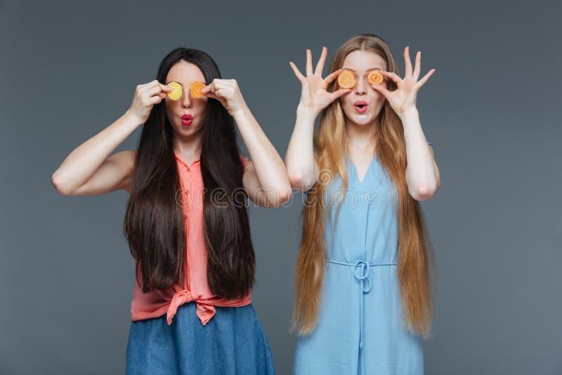 Dwa śmiesznej zadziwiającej kobiety zakrywali ich oczy z marmoladowymi cukierkami obraz royalty free