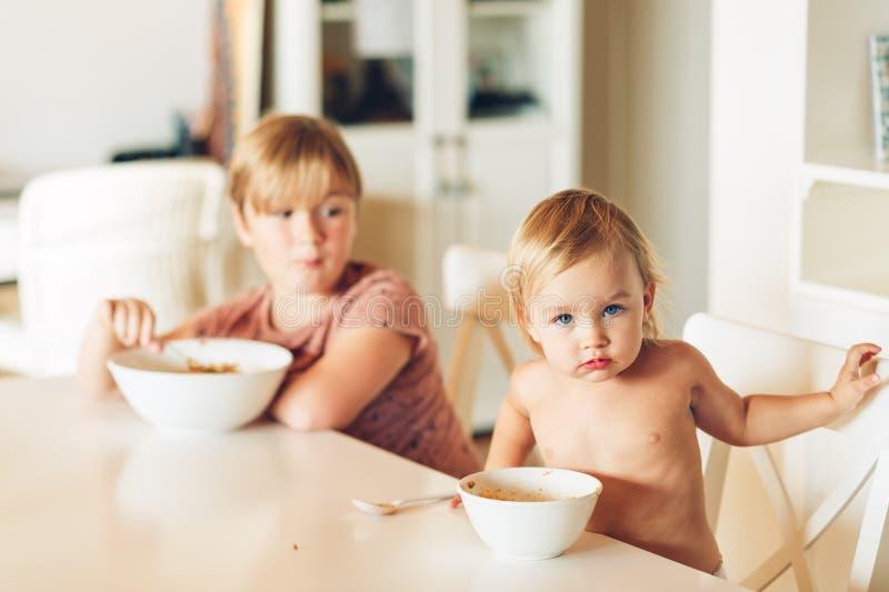 Dwa śmiesznych dzieciaków, chłopiec i dziewczyny łasowania makaronu, je lunch obrazy stock