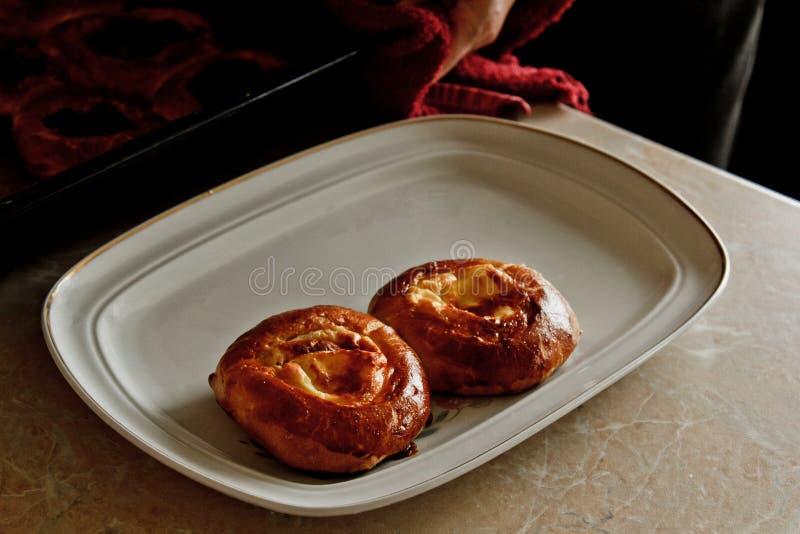 Dwa ?wie?o piec cheesecakes z cha?upa serem k?amaj? na talerzu na kuchennym stole Kulinarny pieczenie wypiekowa przygotowanie sce fotografia stock